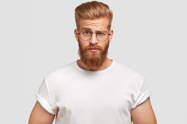 Homem barbudo elegante franze a testa em espanto, insatisfeito com alguma coisa
