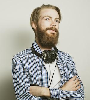 Homem barbudo elegante na camisa. feche o retrato sobre um fundo cinza.