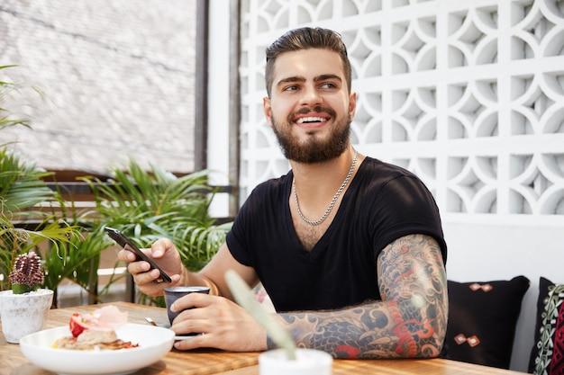 Homem barbudo elegante sentado em um café