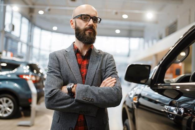 Homem barbudo em copos posa na caminhonete na concessionária. cliente no showroom de veículos, homem comprando transporte, concessionária de automóveis