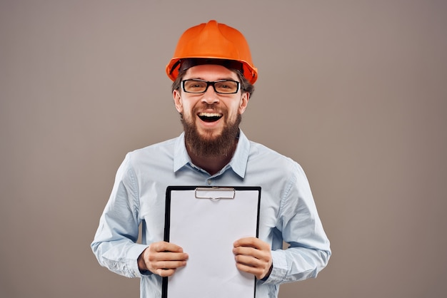 Homem barbudo em documentos de engenheiro de capacete laranja trabalhando