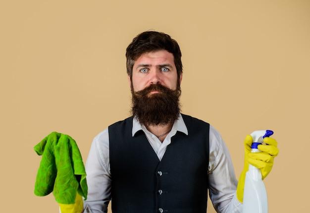 Homem barbudo em luvas de borracha de uniforme com produtos de limpeza limpador de serviço doméstico homem com pano