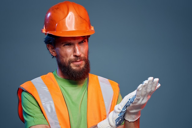 Homem barbudo em luvas de capacete laranja profissional cortada vista de fundo azul. foto de alta qualidade