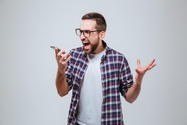 Homem barbudo em óculos, gritando no telefone