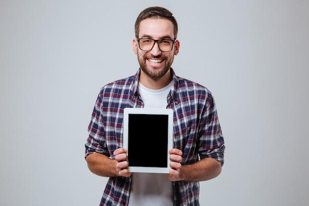 Homem barbudo em óculos mostrando a tela do computador tablet em branco