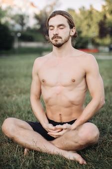 Homem barbudo em pose de lótus, sentado na grama verde, conceito de calma e meditação