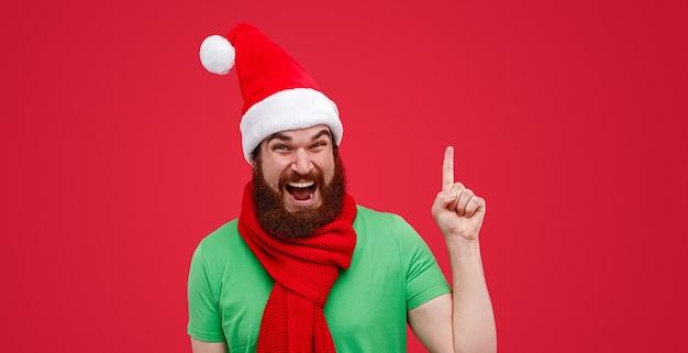 Homem barbudo em roupas de elfo apontando para cima durante o natal