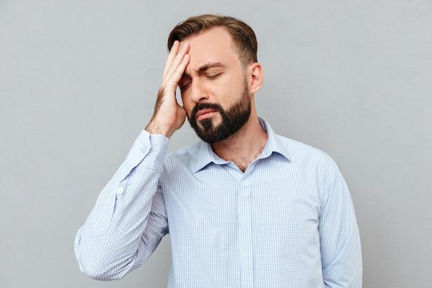 Homem barbudo em roupas de negócios com dor de cabeça e tocando sua testa