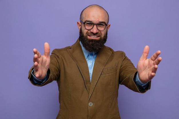 Homem barbudo em terno marrom usando óculos, olhando para a câmera, fazendo um gesto de boas-vindas com as mãos em pé sobre um fundo roxo