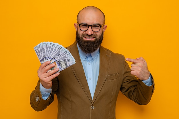 Homem barbudo em terno marrom usando óculos segurando dinheiro, apontando com o dedo indicador para dinheiro, sorrindo alegremente olhando para a câmera em pé sobre fundo laranja