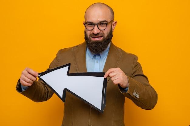 Homem barbudo em terno marrom usando óculos segurando uma seta, olhando para a câmera, feliz e positivo, sorrindo alegremente em pé sobre um fundo laranja