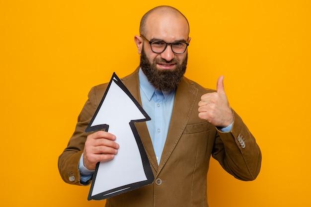 Homem barbudo em terno marrom usando óculos segurando uma seta, olhando para a câmera, sorrindo alegremente e mostrando os polegares em pé sobre um fundo laranja