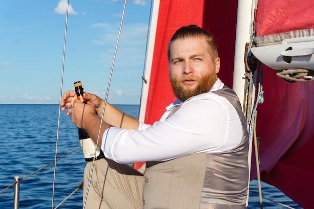 Homem barbudo em um colete com uma garrafa de espumante ao lado do mastro em um veleiro