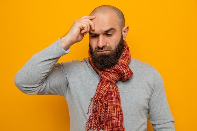 Homem barbudo em um moletom cinza com um lenço em volta do pescoço parecendo perplexo, segurando a mão na testa em pé sobre um fundo laranja