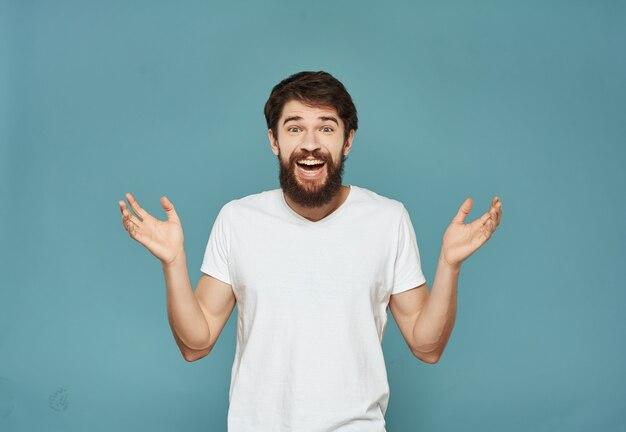 Homem barbudo em uma camiseta branca irritado com expressão facial close up