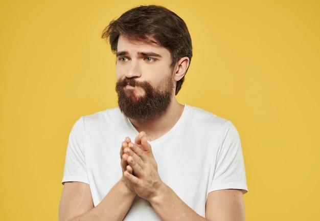 Homem barbudo em uma camiseta branca sério olhar fundo amarelo