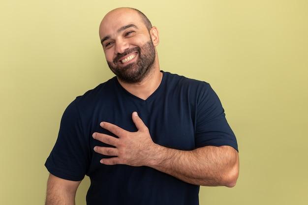 Homem barbudo em uma camiseta preta olhando para o lado sorrindo alegremente, segurando a mão no peito e sentindo-se grato em pé sobre a parede verde