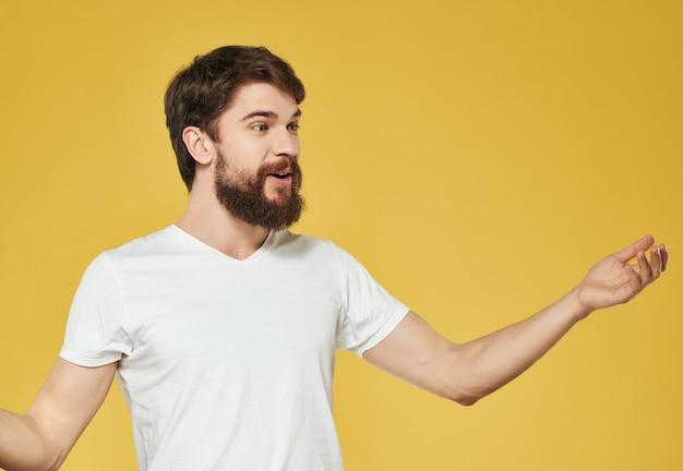 Homem barbudo emocional em camiseta branca com fundo amarelo