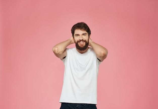 Homem barbudo emocional em estúdio com fundo rosa de camiseta branca