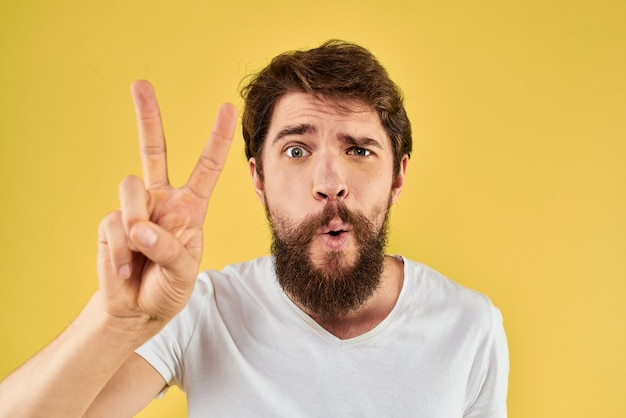Homem barbudo emoções divertido gesto com fundo amarelo de close-up de t-shirt branca de mãos. foto de alta qualidade