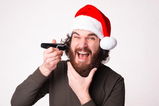 Homem barbudo empolgado, demonstração de descontos para barbeador novo, chapéu de papai noel vermelho