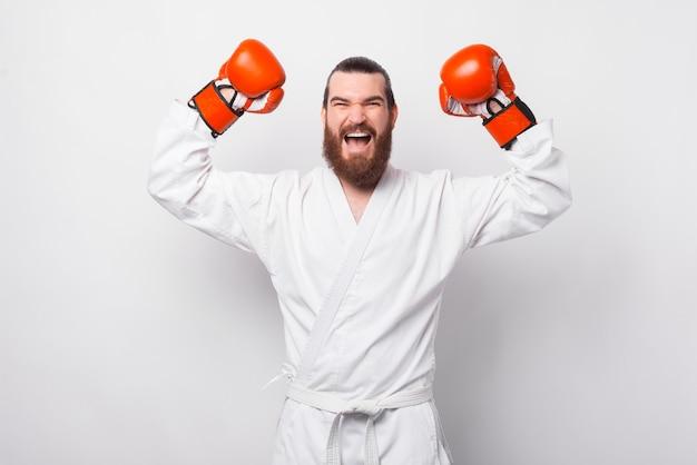 Homem barbudo empolgado e espantado em taekwondo dobok comemorando sobre uma parede branca