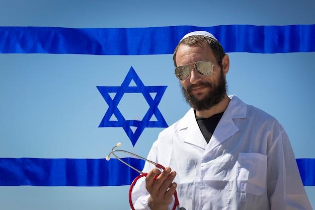 Homem barbudo encantador médico judeu americano em yarmulke branco (chapéu, kipá, chapéu judaico) usando óculos escuros, casaco e estetoscópio no fundo da bandeira de israel. exposição dupla de homem bonito russo