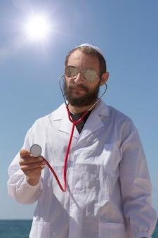 Homem barbudo encantador médico judeu americano em yarmulke branco (chapéu, kipá, chapéu judeu), usando óculos escuros e estetoscópio. homem bonito americano sobre fundo de céu azul. médico brutal de jaleco branco
