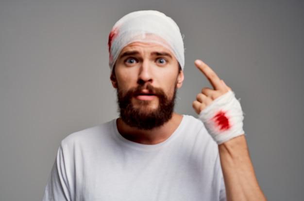 Homem barbudo enfaixado cabeça e mão com fundo isolado de sangue