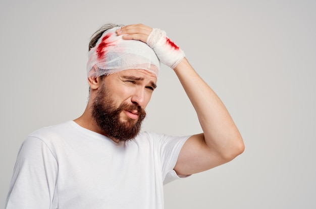 Homem barbudo enfaixado cabeça e mão com luz de fundo de sangue