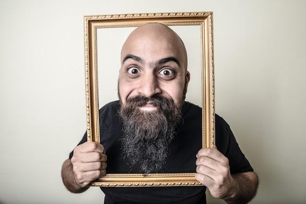 Homem barbudo engraçado com moldura dourada