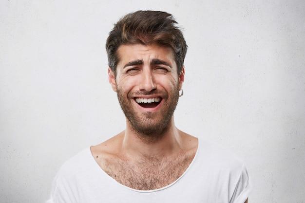 Homem barbudo engraçado positivo com penteado elegante, fechando os olhos enquanto sorria sinceramente. rapaz alegre e atraente com barba escura franzindo a testa de alegria