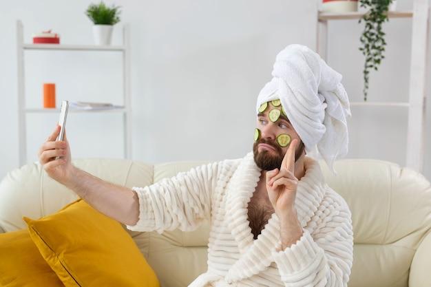 Homem barbudo engraçado segurando fatias de pepino no rosto. spa em casa, corpo e pele para o conceito masculino.