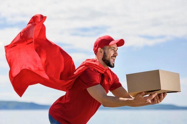 Homem barbudo entrega usando capa de super-herói