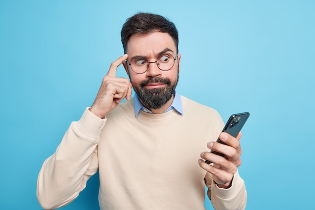 Homem barbudo envergonhado focado no smartphone mantém o dedo na têmpora tenta se concentrar em olhares de informação na tela vestida em poses de suéter arrumadas contra a parede azul. conceito de tecnologia