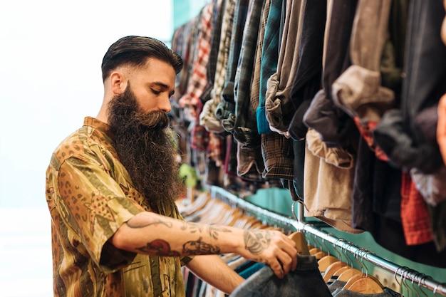 Homem barbudo, escolhendo a camisa pendurada no trilho da loja