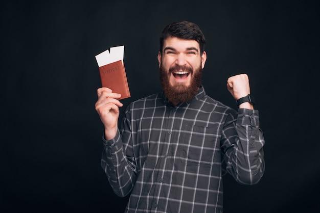 Homem barbudo espantado comemorando e segurando o passaporte com bilhetes