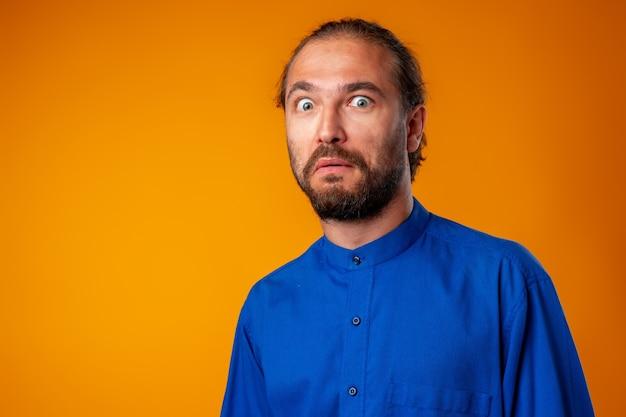 Homem barbudo espantado e confuso olha com espanto