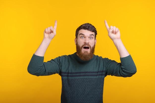 Homem barbudo espantado está apontando para cima com as duas mãos. eu não acredito.