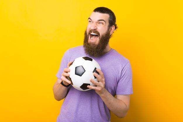Homem barbudo espantado gritando e comemorando a vitória e segurando uma bola de futebol