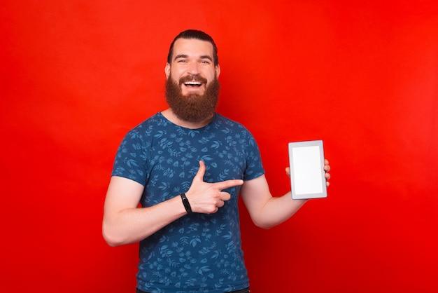 Homem barbudo está apontando para a tela de um tablet.