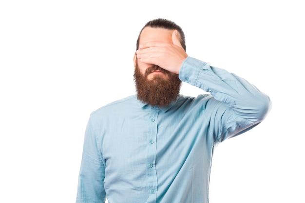 Homem barbudo está cobrindo os olhos sobre fundo branco.