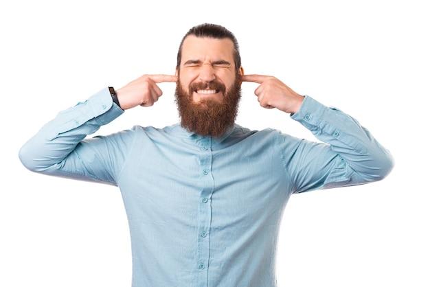 Homem barbudo está fechando as orelhas com os dedos sobre fundo branco.
