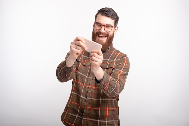 Homem barbudo está gostando de brincar com o telefone em fundo branco.