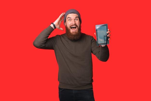 Homem barbudo está segurando e mostrando a tela do tablet para a câmera.