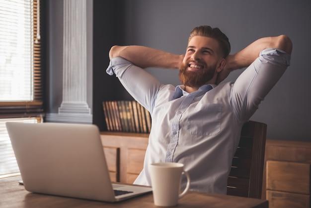 Homem barbudo está sorrindo enquanto relaxa na cadeira no escritório