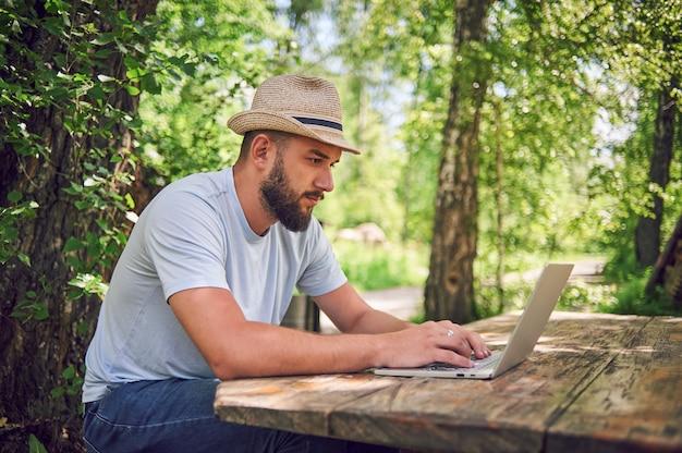 Homem barbudo está trabalhando e sorrindo com o laptop no parque debaixo da árvore. feliz freelancer está sentado e usando o aplicativo ou site na grama. trabalhe remotamente no modo de auto-isolamento