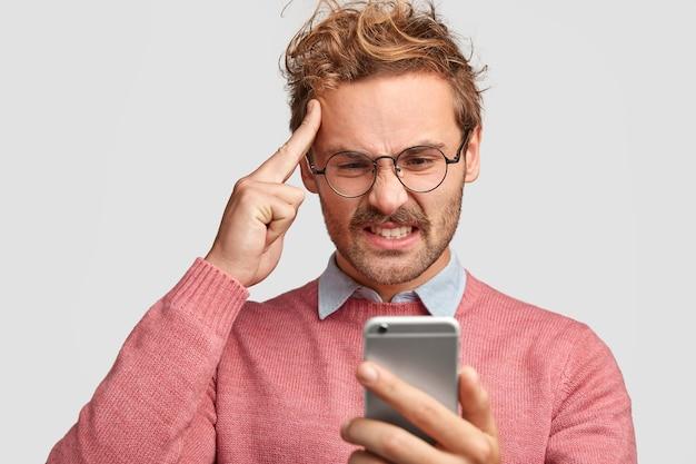 Homem barbudo estressado mantém o dedo da frente na têmpora, olha descontente para o smartphone, franze a testa em desgosto