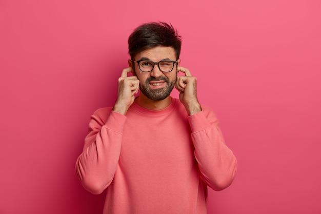 Homem barbudo estressado tapa os ouvidos, ouve sons irritantes