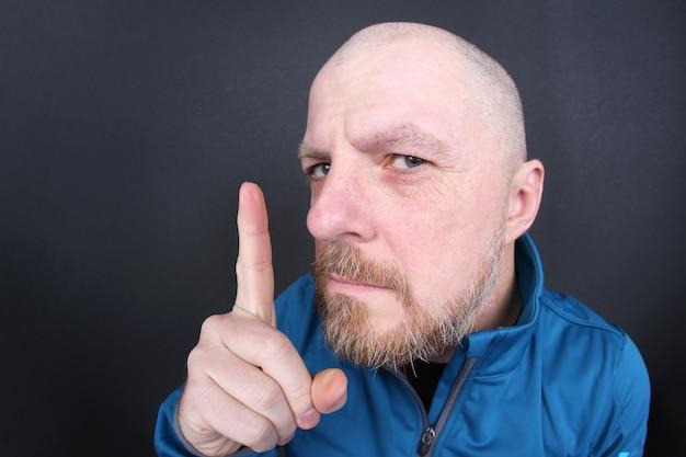 Homem barbudo estrito com um dedo apontando em fundo cinza